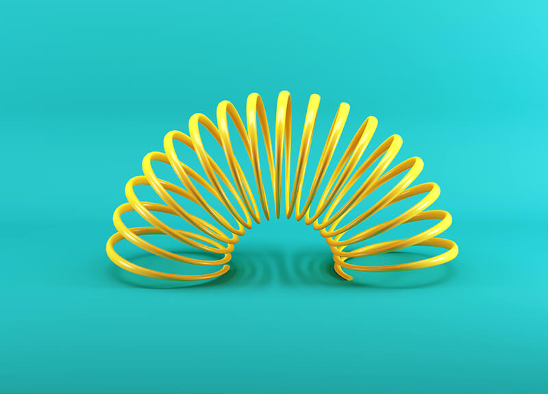 A yellow spring, isolated on a teal background, curved to create a half-moon shape.