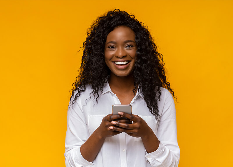 Cheerful woman with long, curly black hair, looking directly at the viewer and holding a mobile phone in her hands.