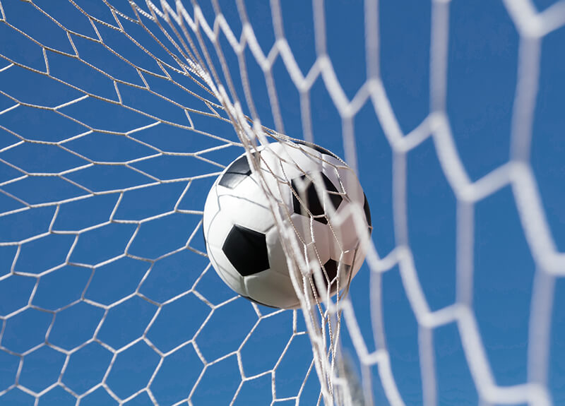 Close-up of a soccer ball making contact with the back of the goal net against a blue sky.