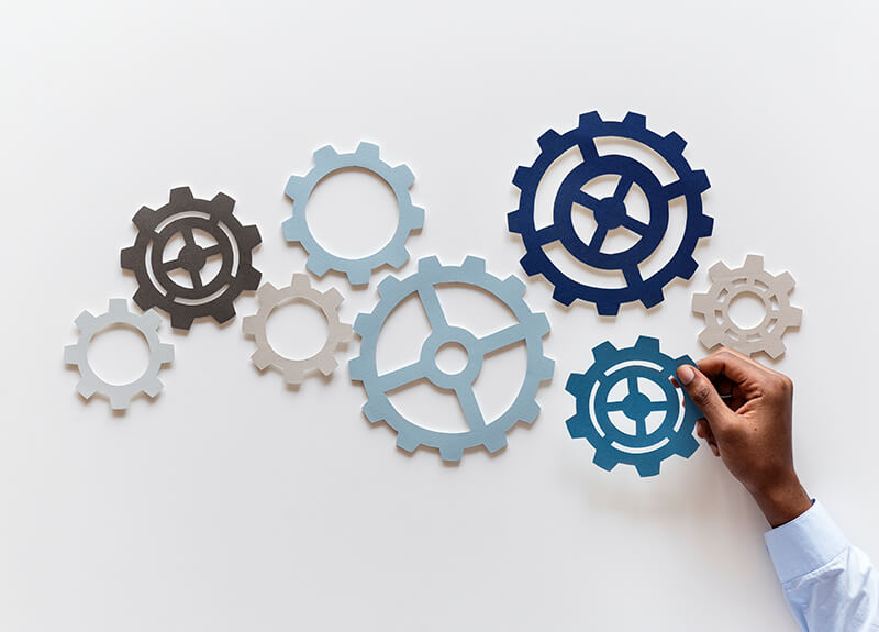 A hand arranging a group of paper gears against a white background.