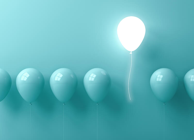 A line of pale blue balloons on a matching pale blue backdrop. One of the balloons is higher than the others, glowing white.