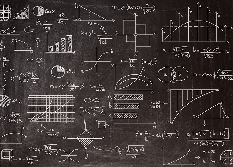 Chalkboard filled with charts, graphs, and mathematical equations.