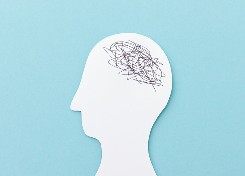 A solid white silhouette of a person's head against a pale blue background. On the area of the head where the brain would be, are a bunch of scribbled lines.