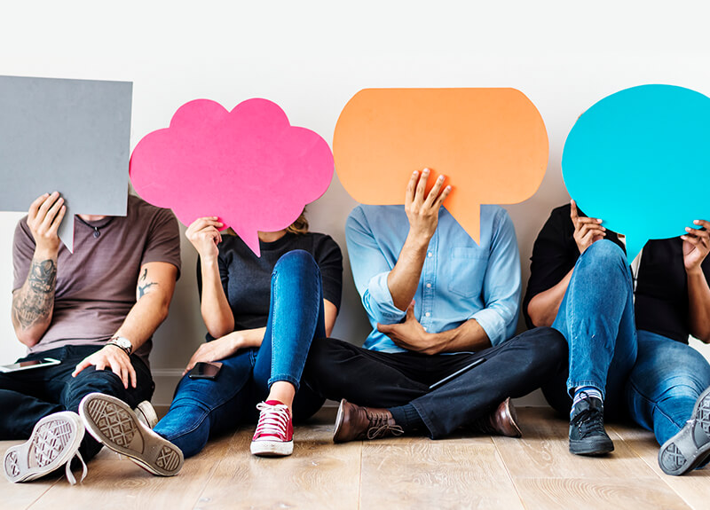 Four people sitting on a wood-paneled floor, holding up colorful speech bubbles in front of their faces.