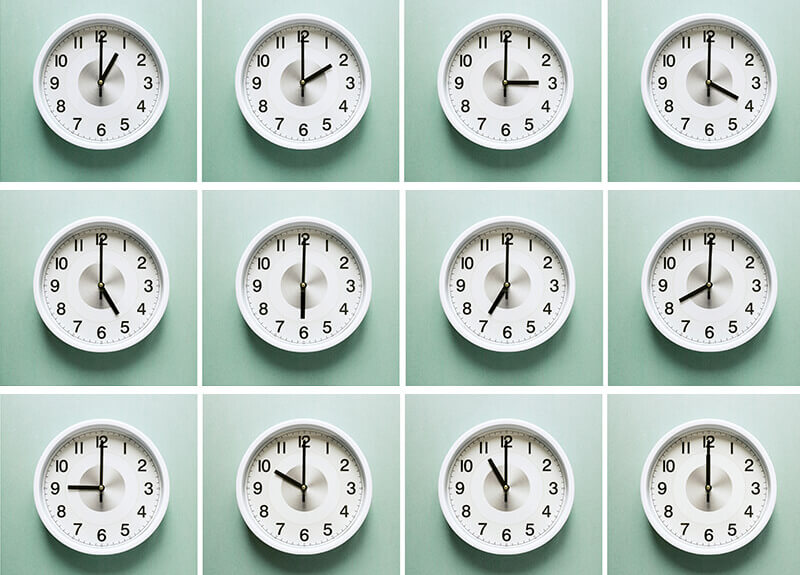 Twelve analog clocks hanging on a pale green wall, each one displaying a different time.