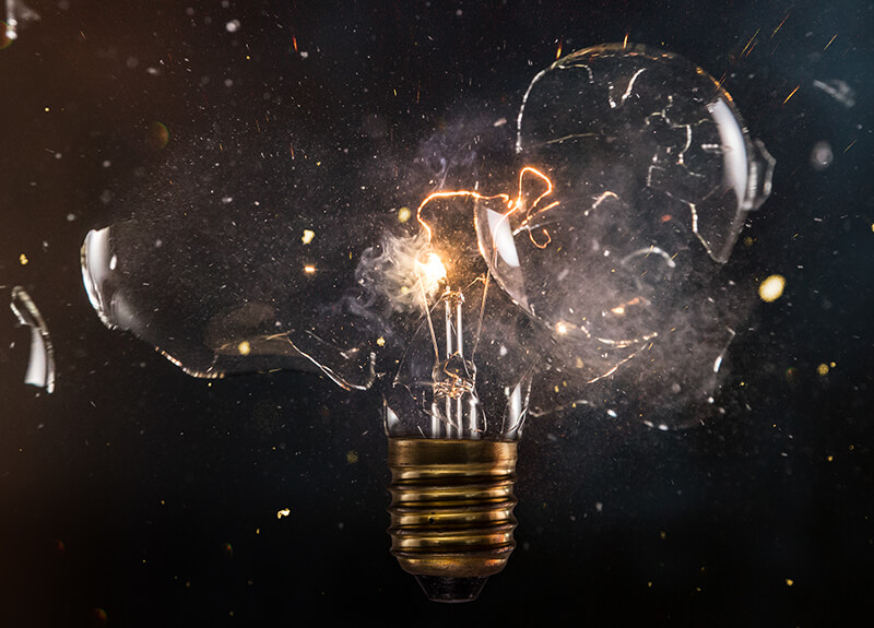 Exploding vintage light bulb on a dark background.