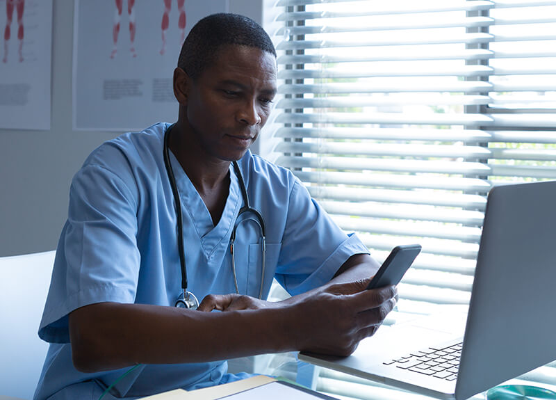 Male nurse with a look of concentration on his face, sitting at a desk looking at his phone.