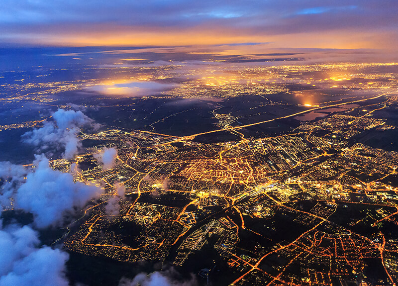 View of a city from a plane at dusk, a small fraction of a cloud in the bottom-left corner. The city lights are bright and make the city blocks and roads visible.i