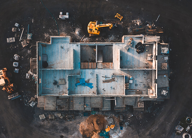 Top-down aerial view of a house's foundation being built. Visible are the divisions between rooms and various construction equipment scattered around the building.
