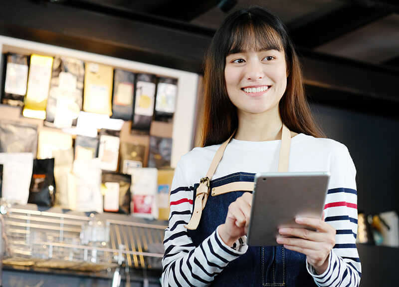 Smiling barista holding and clicking on a tablet while at work.