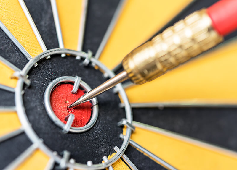 Extreme close-up of a dartboard bullseye, with a metal dart tip piercing the very center.