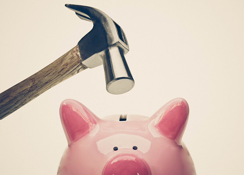Close-up of a hammer being held directly above a pink ceramic piggybank, waiting to smash it open.