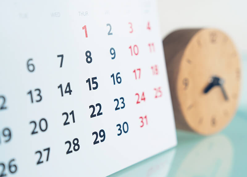 Close-up of a calendar with a blurred wooden clock in the background.