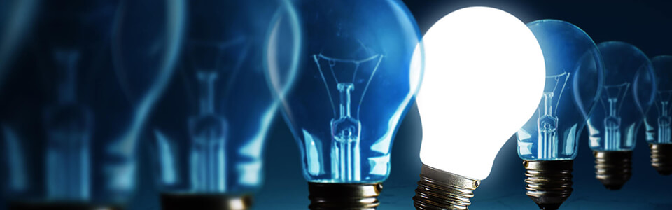 A line of light bulbs against a dark blue background. One light bulb in the line is lit up, the rest remain off.