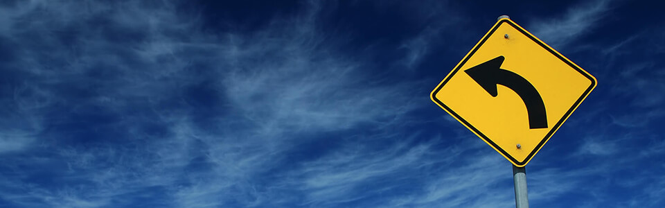 A yellow road sign depicting a curved arrow pointing left against a blue sky.