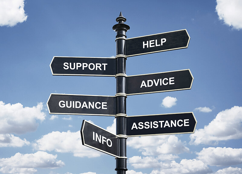 A black signpost with 6 direction arrows against a cloudy blue sky. The arrows say, from top to bottom: help, support, advice, guidance, assistance, and info.