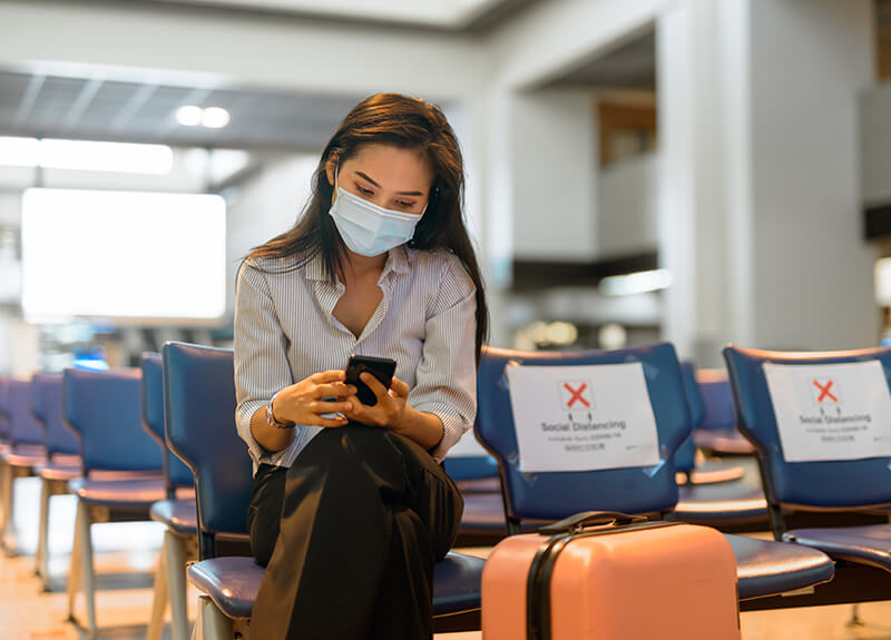 Woman with long brown hair sitting in airport terminal wearing a face mask and looking intently at her phone.