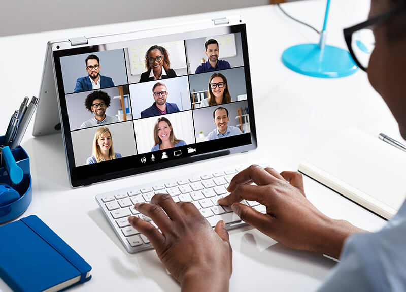 Person using small tablet with keyboard, on a virtual meeting call with 9 coworkers.