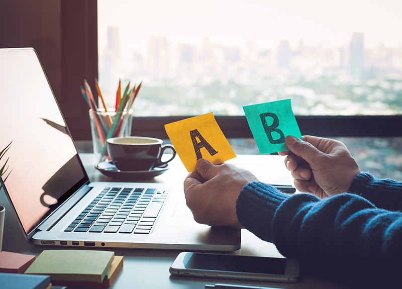 """Two hands resting on a desk with a laptop. The left hand holds a yellow sticky note with a capital """"A"""" written on it. The right hand holds a teal sticky note that has a capital """"B"""" written on it."""