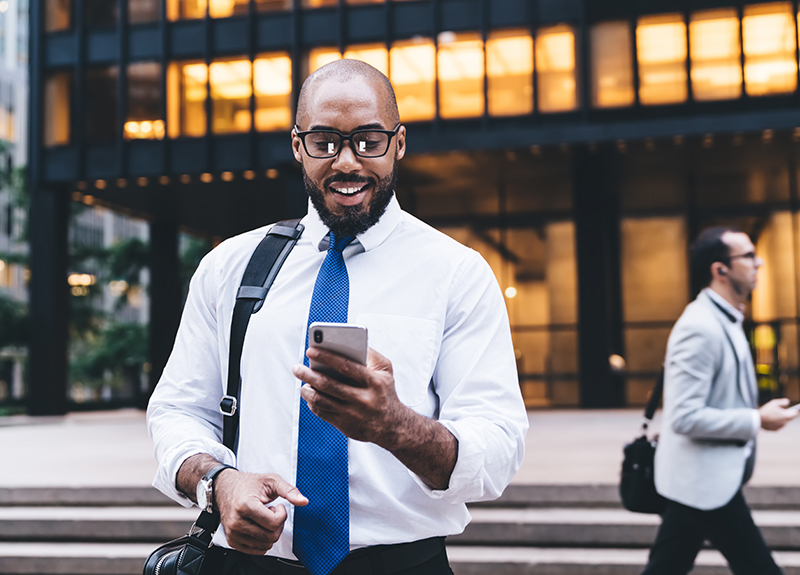 Cheerful bearded business man in glasses walking away from an office building, leather bag hanging off of his right shoulder, looking down at the mobile phone he's holding in his left hand.