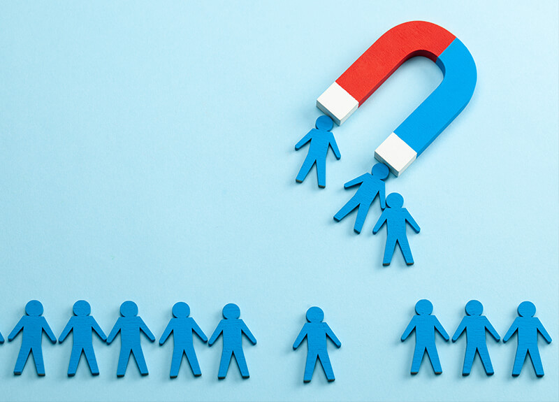 A red and blue u-shaped magnet attracting little metal people.