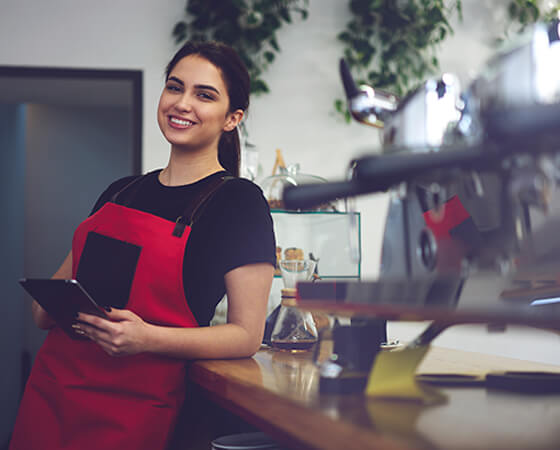 Happy barista in a red apron holding a tablet and leaning on a counter - OttoLearn Agile Microlearning