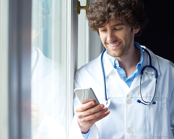 Smiling medical professional holding a smartphone - OttoLearn Microlearning