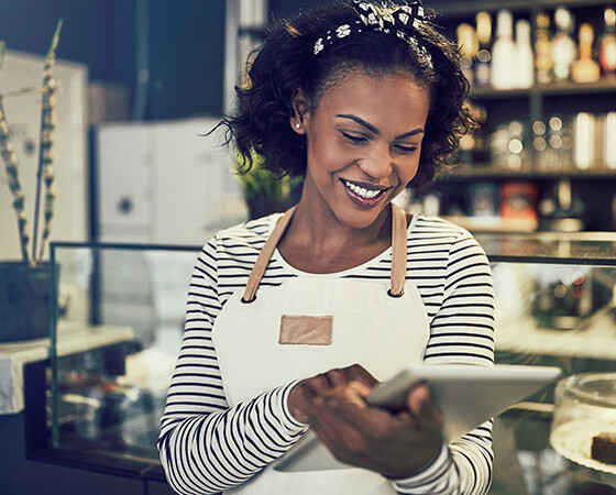 Smiling barista in a white apron looking down at a tablet - OttoLearn Agile Microlearning