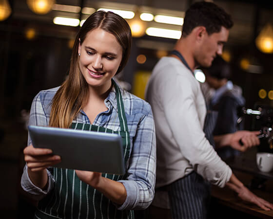 Smiling barista in a green and white striped apron looking down at a tablet - OttoLearn Microlearning