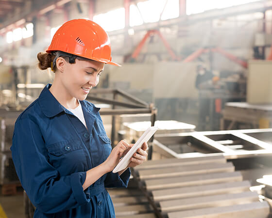 Smiling manufacturer worker in an orange hard hat holding a tablet - OttoLearn Personalized Learning