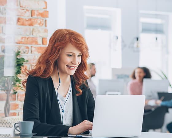 Smiling red-haired individual smiling with earbuds in, looking intently at their laptop - OttoLearn Agile Microlearning