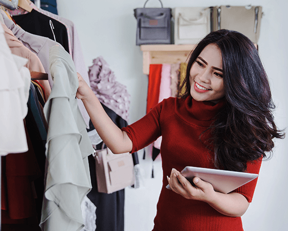 A smiling retail employee holds a tablet in on arm while inspecting a clothing item - OttoLearn Agile Microlearning