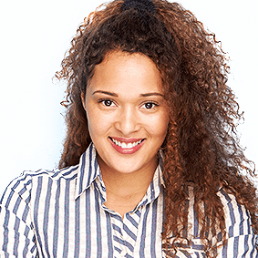 Portrait of a happy woman with thick curly, brown hair, tied back in a half-ponytail. She wears a white and gray, vertically-striped, collared shirt.