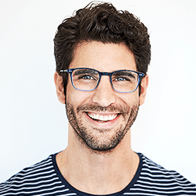 Portrait of a happy man in a striped shirt, with dark brown hair, stubble and glasses.
