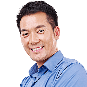 Portrait of a mature & cheerful businessman, with short, dark hair and a blue collared shirt.