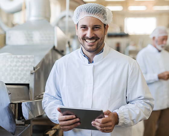 A smiling food manufacturing employee in a white coat and hair net holds a tablet