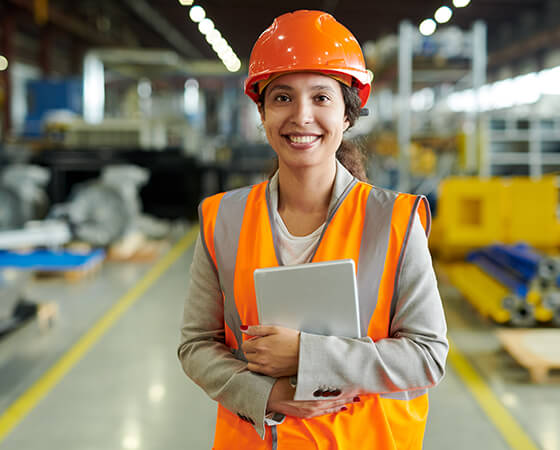 Smiling industrial worker in a hard hat and orange vest holds a tablet in her arms