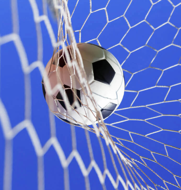 Close-up of a soccer ball that has been kicked into a net against a bright blue sky.