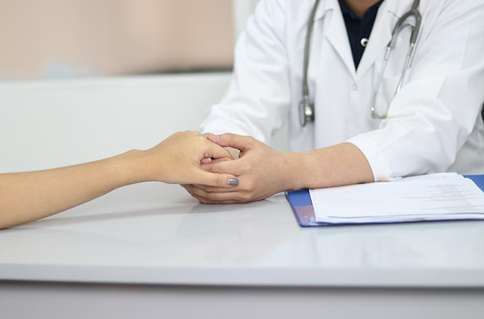 Family medicine physician holding patient's hand