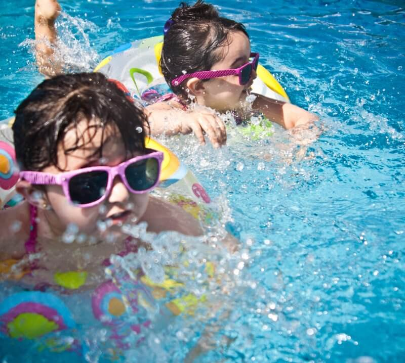 children playing in pool during summer