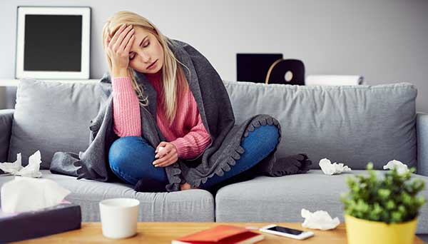 woman sitting on couch sick with covid-19