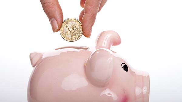 Saving money on healthcare dropping coin into piggy bank
