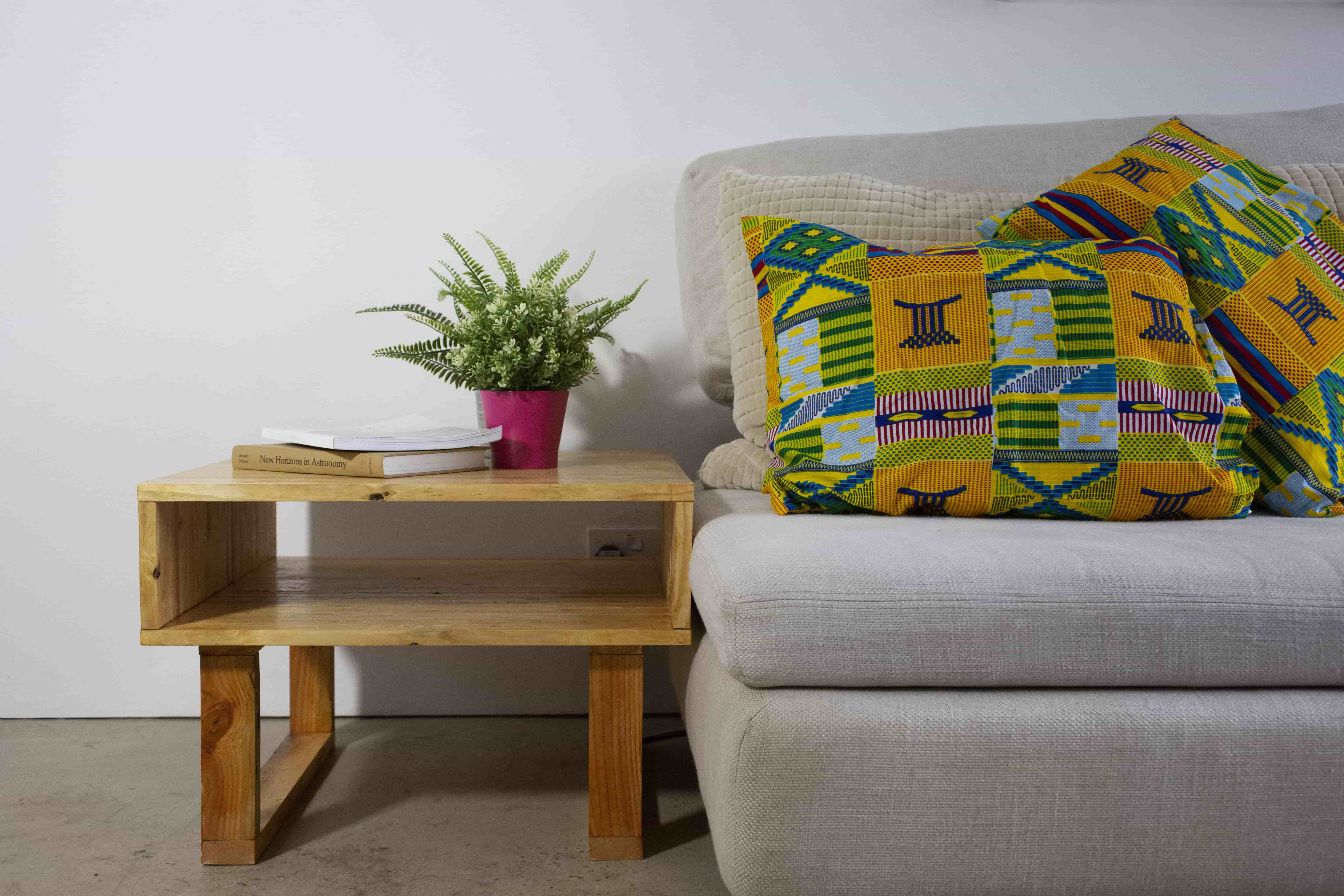 Our upcycled Cowley Side Table next to couch with african printed cushions (InUse-ReUse Furniture)