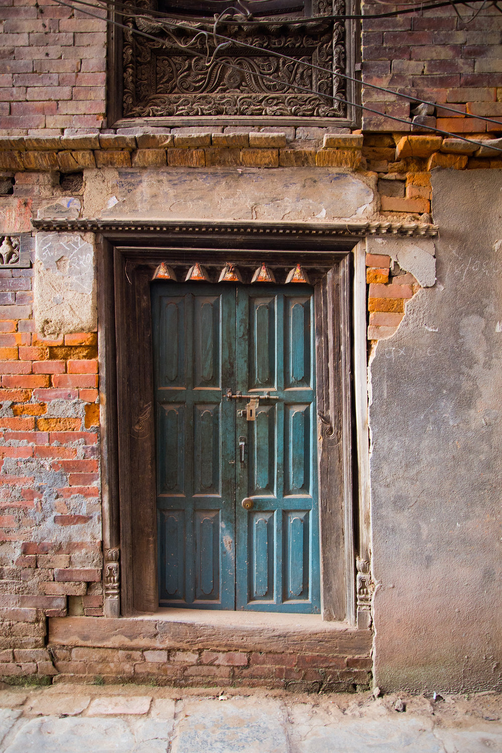 The contrast in color from the door to the bricks is gorgeous. I love all the detail in the frame, also the cracks leading up the side of the building. It's beautiful!
