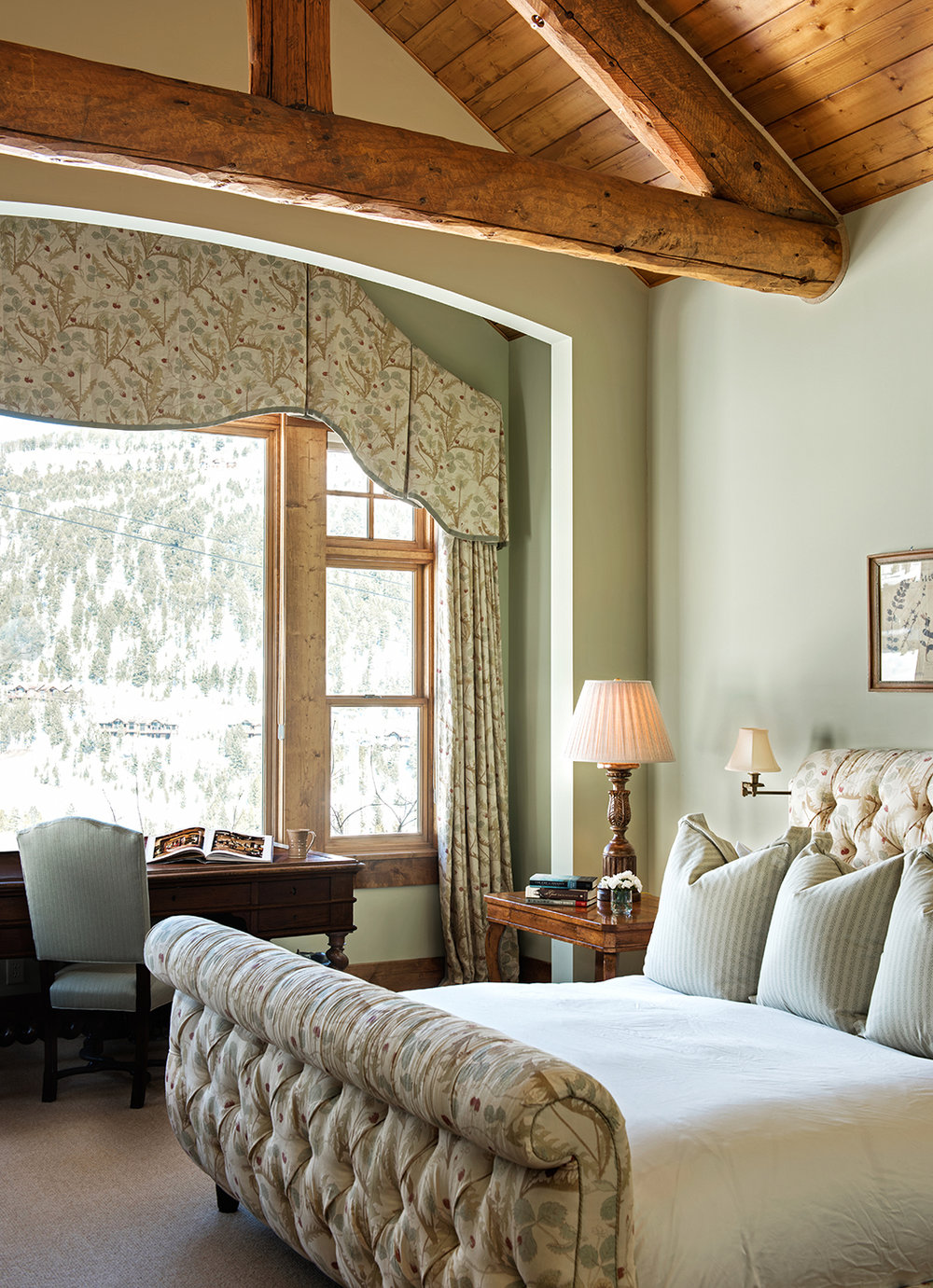 The bedroom is looking out at Pioneer Mountain at Yellowstone Club.  The tall ceilings and classic furnishings add to the grandeur of the space.