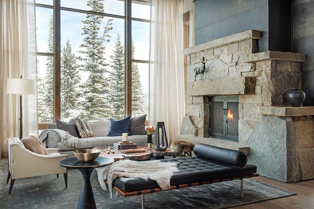 This great room is so stylish but still holds that mountain home feel with the furs and leathers.  I love the light & dark colors used.  It all works so well with the large windows and classic, stone fireplace!