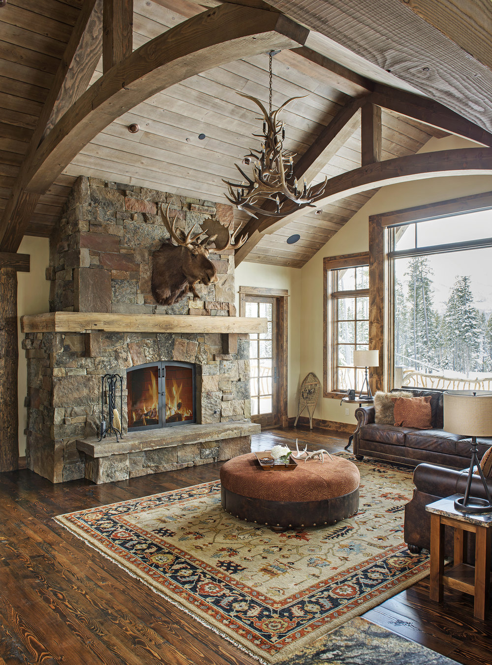 The fireplace, wood paneling on the ceiling, and the animal antler decor that adds to the rustic feel.  Architect -  Centre Sky Architecture  . Builder -  Dovetail Construction