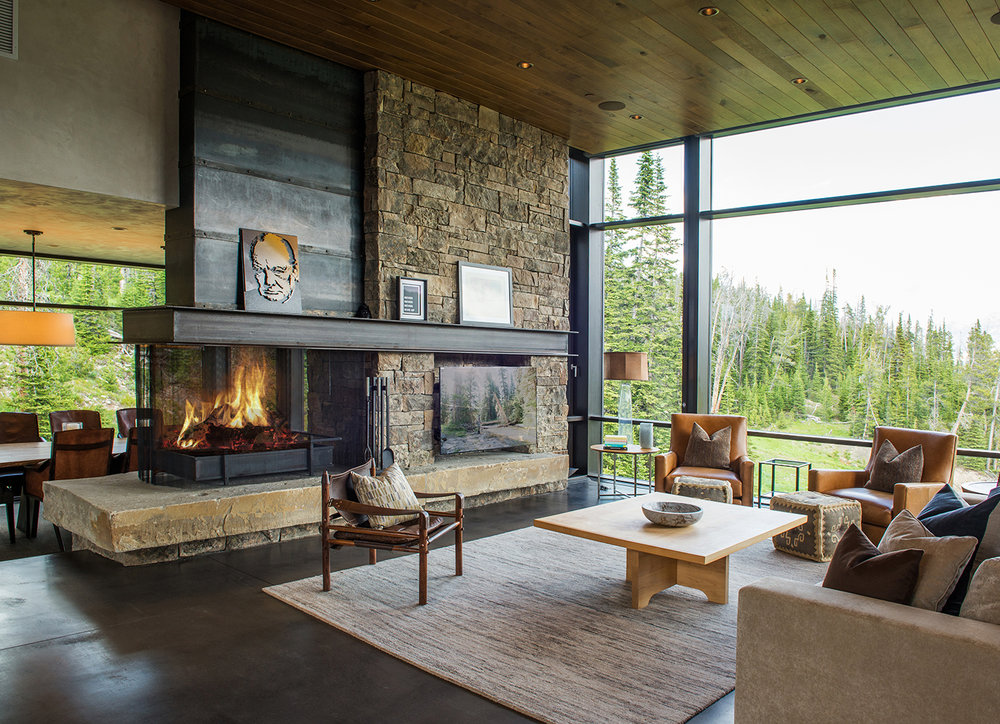 While this is a very modern home the stacked stone fireplace and exposed beams add that sense of rustic elegance. This is a perfect example of the contemporary rustic style. Architect -  Pearson Design Group