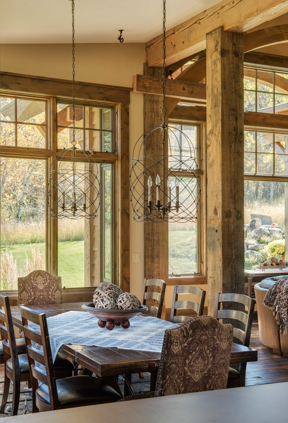 The combination of the strong wood beams and the distressed iron hanging lights are gorgeous in this rustic dining room. Architect -  Reid Smith Architects  Builder -  Schlauch Bottcher Construction