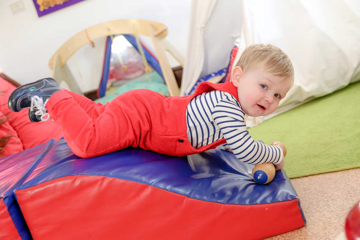 photo of a child playing in a soft-play room